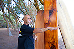 """Tom Pohaku Stone, a native Hawaiian surfer and waterman, also has a masters degree in Pacific Islands Studies.  He has revived the art of carving traditional """"wave sliding"""" boards (surfboards) and Hawaiian sleds.  He is pictured here with three of his hand crafted boards made from three different kinds of native wood."""