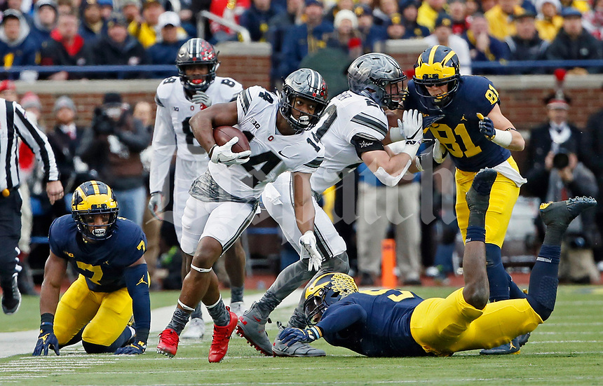 Ohio State Buckeyes wide receiver K.J. Hill (14) pushes down Michigan Wolverines linebacker Mike McCray (9) during a punt return during the 1st half of their game at Michigan Stadium on November 25, 2017.  [Kyle Robertson\ Dispatch]