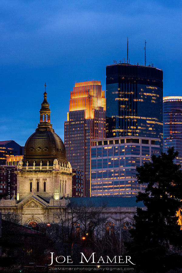Minneapolis skyline at sunset with the Basilica, IDS Tower,  and Wells Fargo Tower.