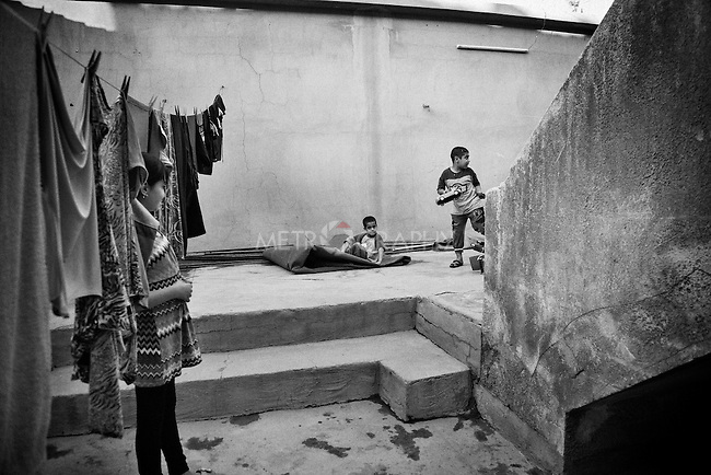 4.4..2015, Kirkuk,Iraq: Marta watching Abdullah (8 years old) and the other kids while they play in the patio shared by the two families.