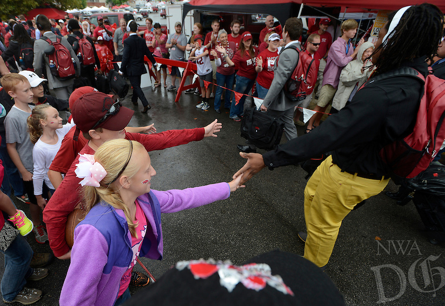 STAFF PHOTO ANTHONY REYES • @NWATONYR<br /> Hadley Casey, 10, of Bentonville, slaps hands with passing players Saturday, Sept. 6, 2014 before the University of Arkansas' football game against Nicholls State in lot 56 in Fayetteville. This is the first home game of the season and the Razorbacks hope to break a 10 game losing streak.