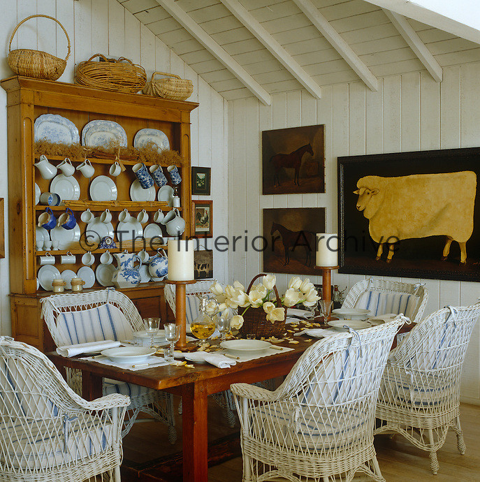 A large Welsh dresser displays a collection of blue and white china in this cosy white-painted dining room