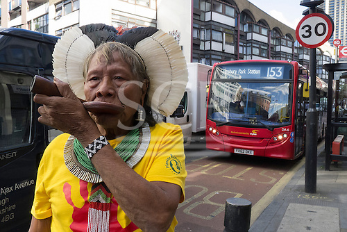 10 June 2014. Kayapo Chief Raoni Metuktire during his visit to London. The chief stands on the street, smoking his pipe, with a single-decker red London bus behind him.