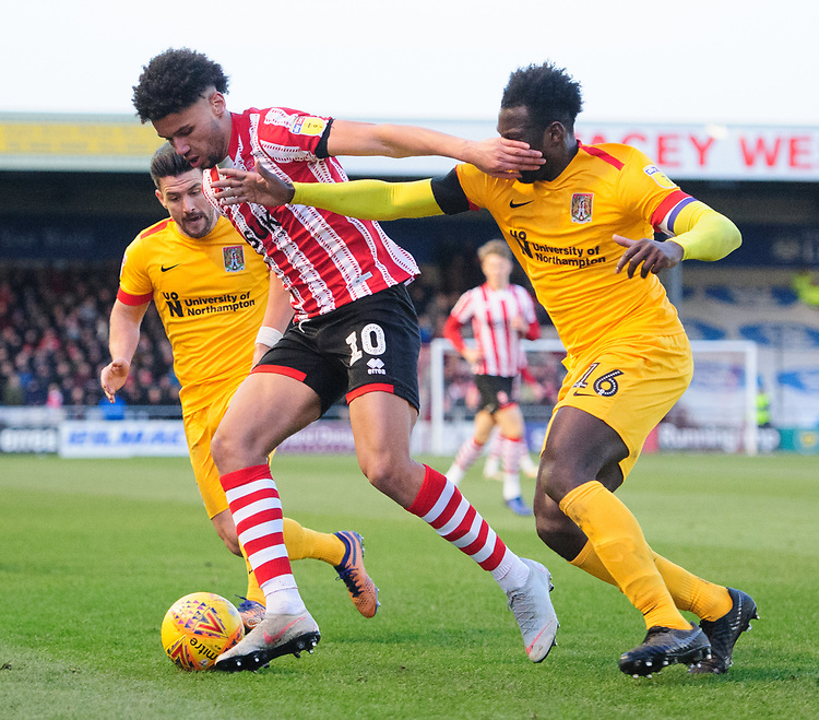 Lincoln City's Lee Angol shields the ball from Northampton Town's Aaron Pierre<br /> <br /> Photographer Chris Vaughan/CameraSport<br /> <br /> The EFL Sky Bet League Two - Lincoln City v Northampton Town - Saturday 9th February 2019 - Sincil Bank - Lincoln<br /> <br /> World Copyright © 2019 CameraSport. All rights reserved. 43 Linden Ave. Countesthorpe. Leicester. England. LE8 5PG - Tel: +44 (0) 116 277 4147 - admin@camerasport.com - www.camerasport.com