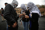 Masked Palestinian protesters use sling shots to throw stones towards Israeli security forces during clashes near the Jewish settlement of Beit El, near the West Bank city of Ramallah October 27, 2015. The current round of violence began last month with clashes at Jerusalem's most sensitive holy site, clashes quickly spread to other areas of east Jerusalem, across Israel and into the West Bank and Gaza Strip. Photo by Shadi Hatem