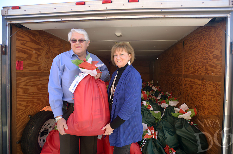 NWA Democrat-Gazette/BEN GOFF @NWABENGOFF<br /> Johnny Bakker (CQ) and wife Susan Chase, organizers of the Chase Family Foundation, pose for a photo on Sunday Dec. 6, 2015 as volunteers with the Chase Family Foundation distribute bags of food for home-bound seniors and their pets. The organization's annual holiday distribution seeks to provide enough food for seniors and their pets to get through the holidays and periods of inclement whether when Meals on Wheels doesn't operate.