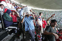 United States Men's National team fans cover themselves from water bottles, beer, and other objects are thrown at  by Mexican fans at Azteca stadium. The United States Men's National Team played Mexico in a CONCACAF World Cup Qualifier match at Azteca Stadium in, Mexico City, Mexico on Wednesday, August 12, 2009.