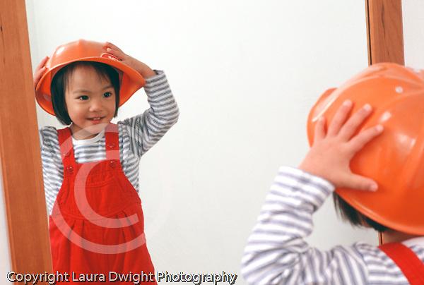 Nineteen month old girl closeup wearing play hat recognizing self in mirror horizontal Asian Vietnamese