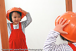 Nineteen month old girl closeup wearing play hat recognizing self in mirror horizontal Asian Vietnamese