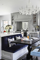 The deep blues, soft whites and pale blues continue into the kitchen's furnishings, while a chandelier adds another soupcon of glamour to the interior