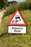 Red triangle road sign warning of Slippery Road, Suffolk, England, Uk