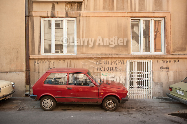 "A compact red-colored Yugo coupe parks in a space labeled ""No Parking"" on Niska Street, Beograd"