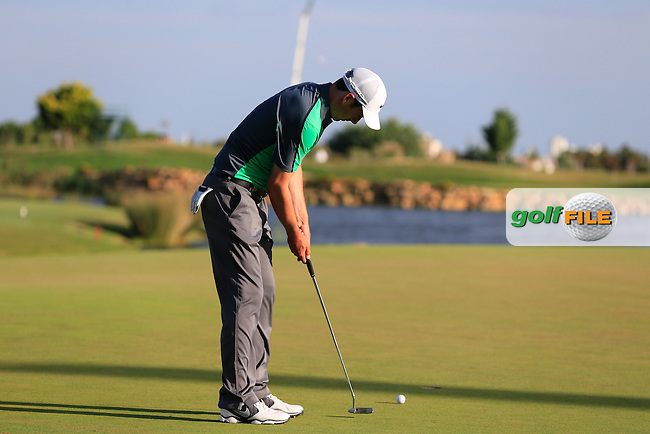 Ross Fisher (ENG) putts on the 18th green during Saturday's Round 3 of the 2013 Portugal Masters held at the Oceanico Victoria Golf Club. 12th October 2013.<br />