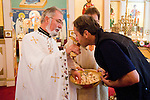 Liturgy service at St. Sava Orthodox Church, Jackson, Calif...Father Stephen Tumbas assisted by Dan Stojanovich present bread as Miloje Milinkovic kisses the golden cross in respect.