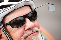 Morehead City, NC -- A rearview mirror attached to Paul Kelly's glasses. Quadriplegic hand cyclist Paul Kelly, 62, trains for the Boston Marathon Tuesday, March 27, 2018. (Justin Cook for The Wall Street Journal)<br /> <br /> SUMMARY:<br /> <br /> Paul Kelly, hand cyclist, Beaufort, NC Training for the Boston Marathon so we would want to shoot in March to run the week before the marathon or marathon Monday, Apriln16. Life as a quadriplegic doesn't keep 62-year-old Paul Kelly on the sidelines. After breaking his neck in a swimming accident in 1978, Kelly was determined to find fitness activities to maintain an active lifestyle. He discovered handcycles while watching his niece compete in the 2006 Marine Corps Marathon and was inspired to start his own marathon career to stay fit. Paul has competed in over 100 half and full marathons. On April 16, he will celebrate his 40th year of living as a quadriplegic by taking on one of the most coveted races for a marathoner -- the Boston Marathon. Kelly is among the 60 handcyclists competing in the 2018 Boston Marathon with a qualifying time of 1:26:37. Most of Paul's distance training takes place at Bogue Banks, which includes Atlantic Beach, Salter Path, and Emerald Isle, N.C. It's Nicholas Sparks worthy scenery with its marshes, waterways, inlets and small islands. Paul is particularly fond of the approach from Atlantic Beach to Bogue Banks -- it's via the high-rise bridge. In cold weather, Paul has to be mindful of the environment and dress in a manner that insulates his legs while also allowing his upper body to ventilate. Paul chooses to train at times of day when the temperatures are more reasonable. He uses hand warmers in his gloves, on the inside the grips on his handcycle and in the legs of his trousers.
