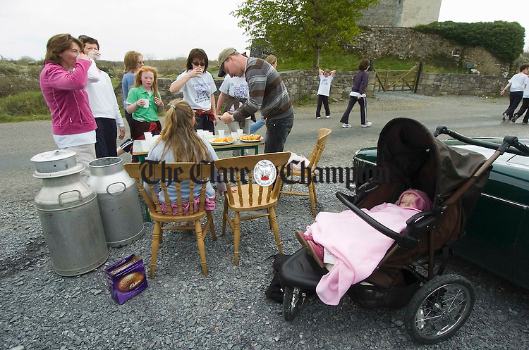 ...Baby Maeve Cahill sleeps in her pram as her dad Eamon Cahill provides welcome refreshments for weary competitors at the Sonny Murphy memorial roadrace in Kilnaboy. Photograph by John Kelly.