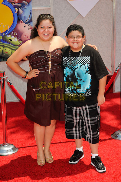 """RAINI & RICO RODRIGUEZ .at the world premiere of World Premiere of Disney Pixar's """"Toy Story 3"""" at El Capitan Theatre in Hollywood, California, USA, June 13th, 2010..arrivals full length strapless dress hand on hip brown family brother sister siblings .CAP/ROT.©Lee Roth/Capital Pictures"""