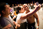 Lucha Libre AAA wrestler Rocky Romero poses with a fan ringside in Sacramento, CA March 28, 2009.