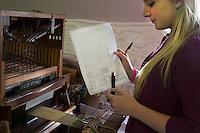 Creatrice dei tessuti al lavoro con un piccolo telaio per campionature e tabella dei colori e dei filati Bute tartan mills
