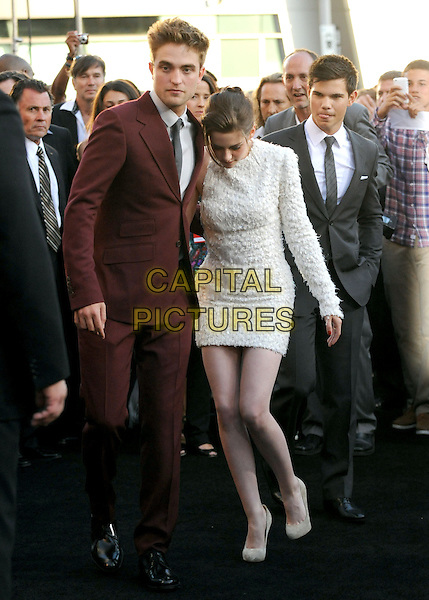 ROBERT PATTINSON & KRISTEN STEWART.The premiere of The Twilight Saga : Eclipse held at the Los Angeles Film Festival at Nokia Live in Los Angeles, California, USA..June 24th, 2010    .full length white one sleeve dress beige cream shoes red maroon burgundy suit black tie grey gray shirt looking down couple rob.CAP/RKE/DVS.©DVS/RockinExposures/Capital Pictures.