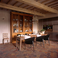 A country dining room with a beamed ceiling a tiled floor. A chandelier hangs from the ceiling above a simple wooden table laid for lunch. A contemporary bank of stainless steel kitchen units and modern dining chairs contrasts with the original period features.