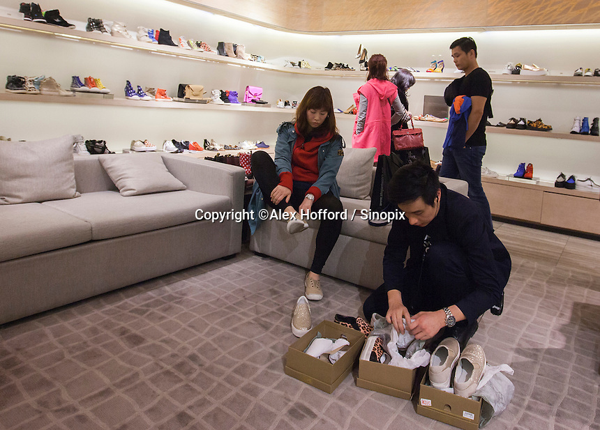 A woman tries on shoes in Lane Crawford, a Hong Kong-based luxury goods department store, Hong Kong, China, 07 March 2014. Hong Kong is known as a shopping mecca for luxury goods due to the fact that such goods are sold tax free in the ex-British colony, in contrast to mainland China where high taxes are still slapped on luxury goods.