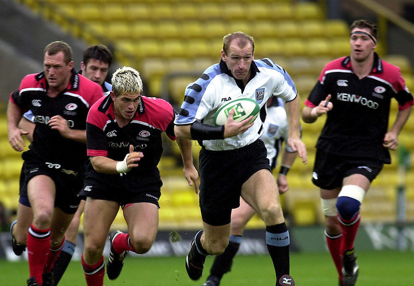 Photo  Pic John Cassidy .21/10/00.Heineken Cup Saracens v Cardiff at Vicarage Road..Saracens.Cardiffs Gareth Thomas breaks away from Saracens Ben Johnston