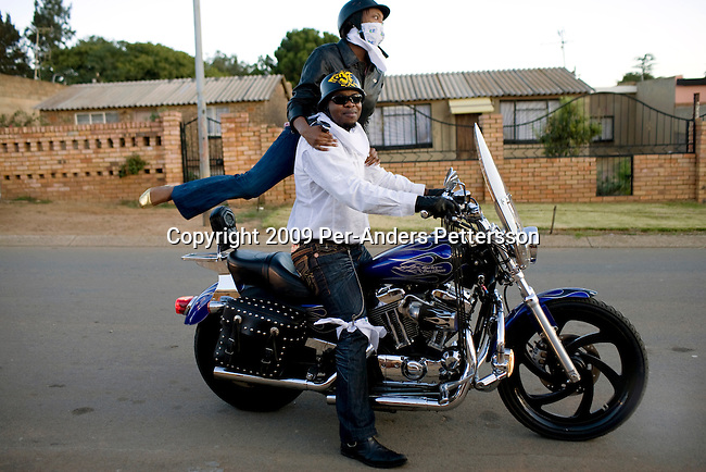 SOWETO, SOUTH AFRICA MARCH 8: Afrika Tau, age 31, picks up a friend with his Harley Davidson motorcycle on March 8, 2009 in Soweto, South Africa. He grew up in Soweto and he is now a successful executive working for Cisco and lives in a house in Kyalami, a wealthy suburb north of Johannesburg. He drives a new BMW and relaxes with his motorbike on the weekends. Afrika is one of the recent educated and affluent black people that has grown up in the poor townships but now are living a middle-class or affluent life in the former white suburbs. (Photo by: Per-Anders Pettersson)