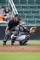 Kannapolis Intimidators catcher Brett Austin (10) sets a target as home plate umpire Jeff Gorman looks on during the game against the Charleston RiverDogs at CMC-NorthEast Stadium on June 27, 2014 in Kannapolis, North Carolina.  The Intimidators defeated the RiverDogs 6-5.  (Brian Westerholt/Four Seam Images)