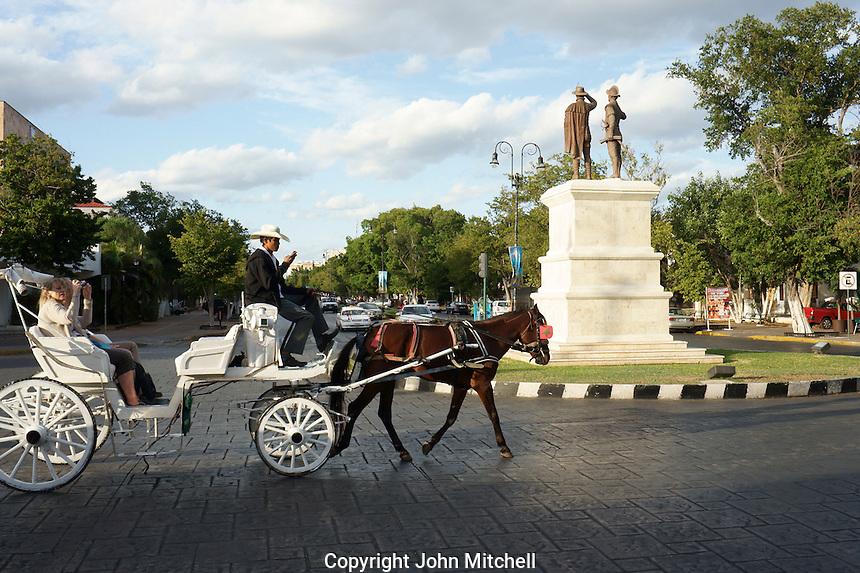 Tourists riding in a horse drawn carriage or calesa on Paseo de Montejo, Merida, Yucatan, Mexico.....