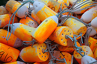 Brightly colored orange marker buoys, floats used for commercial crabbing, fishing and lobstering, Port of Astoria, Oregon, OR, America, USA.