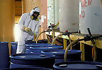 Hazardous material warehouse worker taking sample
