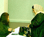McLean, VA - December 13, 2005 -- Fatima Youssif, right, who emigrated to Binghamton, New York from Duhua, Iraq to escape being gassed by Saddam Hussein, receives her ballot from an unidentified poll worker in the Iraqi election in McLean, Virginia on December 13, 2005. .Credit: Ron Sachs / CNP.(RESTRICTION: NO New York or New Jersey Newspapers or newspapers within a 75 mile radius of New York City)