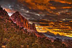 Wet from a recent snowstorm, the peaks of the Zion Mountains glow orange and yellow in the last sunset light.