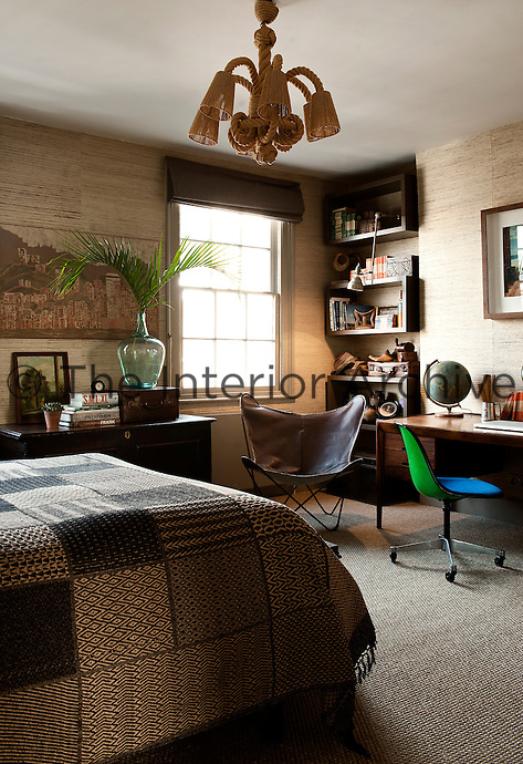 A guest bedroom that doubles as a home office, features a conglomerate of exotic furniture pieces and collectables giving the room an other-worldly, exotic feel, such as the  rosewood Danish desk, which is from the 1960s. This theme is beautifully accentuated by a textured Philip Jeffries wallpaper made of split bamboo on grass cloth.