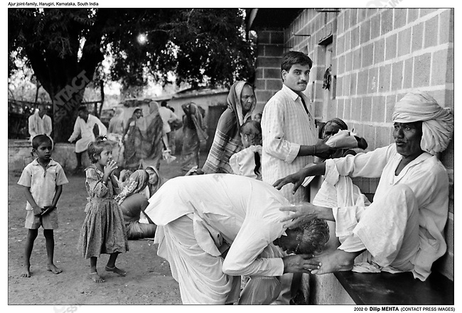 Every year the family celebrates the death anniversary of their parents. One event that marks this is the handing out of new clothes to all the family members. In this photograph a family member has received a shirt and a pair of trousers and he thanks the Patriarch by clasping his feet with his hands and as a mark of further respect touching his forehead to the Patriarchs feet as well...
