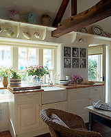 In the traditional cream-painted kitchen a collection of antique jugs hangs from open shelves above the butler's sink