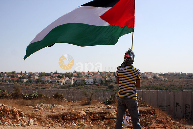 A Palestinian youth waves a flag during a protest against Israel's controversial separation barrier in the West Bank village of Nilin, near the Palestinians city of Ramallah,on Nov. 5, 2010. Clashes erupted during the weekly demonstrations, which are aimed at halting the construction of Israel's controversial separation barrier that is mostly built inside the occupied territory and cuts off farmers from their land in border communities like Nilin.. Photo by Issam Rimawi