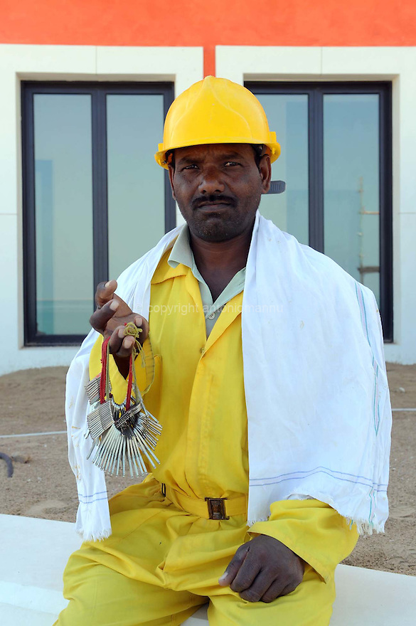 Doha Qatar novembre 2010. Operaio indiano impegnato nella costruzione dello sviluppo immobiliare The Pearl. Una parte è liberamente ispirata all'architettura di Venezia. An Indian worker at the construction siteof the new real estate development The Pearl a part of which is freely inspired  by Venezia's architecture.