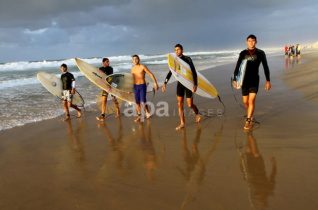 Palestinian youths practise their sport ( riding the waves ) during sunset in Gaza city beach on Dec. 6,2010. Photo by Ashraf Amra