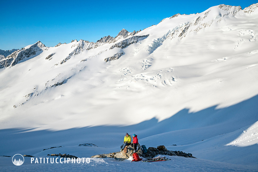 Two skiers relaxing in the sun while on the Berner Haute Route, Switzerland