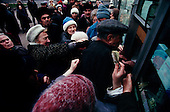 "Moscow, Russia<br /> October 22, 1992<br /> <br /> People fight to purchase cigarettes, for resale, at a kiosk near Kievski train station. The early days of the ""rezbourka"", a business sorting out that left many dead throughout Russia in the 1990's.<br /> <br /> In December 1991, food shortages in central Russia had prompted food rationing in the Moscow area for the first time since World War II. Amid steady collapse, Soviet President Gorbachev and his government continued to oppose rapid market reforms like Yavlinsky's ""500 Days"" program. To break Gorbachev's opposition, Yeltsin decided to disband the USSR in accordance with the Treaty of the Union of 1922 and thereby remove Gorbachev and the Soviet government from power. The step was also enthusiastically supported by the governments of Ukraine and Belarus, which were parties of the Treaty of 1922 along with Russia.<br /> <br /> On December 21, 1991, representatives of all member republics except Georgia signed the Alma-Ata Protocol, in which they confirmed the dissolution of the Union. That same day, all former-Soviet republics agreed to join the CIS, with the exception of the three Baltic States."