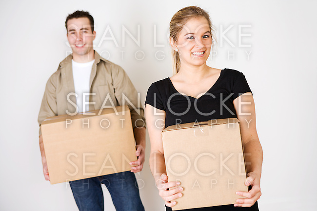Young couple, indoors, packing posessions in cardboard boxes.