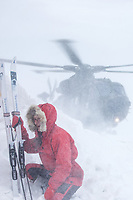 Kaisa-Wenche Vivisdatter holding on to her skies as  British soldiers arrive by helicopter to deliver firewood to a remote Norwegian cabin. The newly built Vouma cabin in Dividalen National Park is part of the Norwegian Trekking Association network. As a goodwill gesture and part of their Arctic training the Royal Navy use helicopters to fly firewood to the remote location. <br /> <br /> <br /> In 2019 the Arctic exercise Clockwork passed 50 years of training in Norway, and now has a permanent base within the Norwegian Air Force base at Bardufoss. <br /> <br /> 845 Naval Air Squadron is a squadron of the Royal Navy's Fleet Air Arm. Part of the Commando Helicopter Force, it is a specialist amphibious unit operating the Leonardo Commando Merlin Mk3 helicopter and provides troop transport and load lifting support to 3 Commando Brigade Royal Marines.<br /> <br /> ©Fredrik Naumann/Felix Features