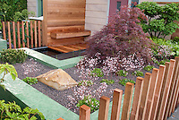 Beautifully landscaped entry of house with Japanese maple tree in spring, Saxifraga in flowers, fence, stones, boulders, wood and upscale touches creating a sense on an outdoor room enclosed by open posts. Small garden design, pebble mulch, simplicity, saxifraga plants.