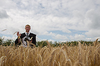 A Calvinistic priest blesses the wheat field during a traditional harvest festival in Opalyi (some 280 kilometers East of capital city Budapest), Hungary on July 13, 2013. ATTILA VOLGYI
