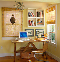 A simple wooden trestle table serves as a work space in a corner of this sunlit living room