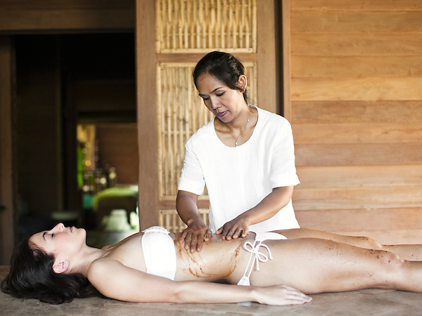 A woman receives a body scrub made of crushed coconut shell, orange extracts and rosemary extracts, a scrub made to exfoliate and smoothen oily skin. The Spa at Six Senses Hideaway Yao Noi, Koh Yao Noi, Thailand.