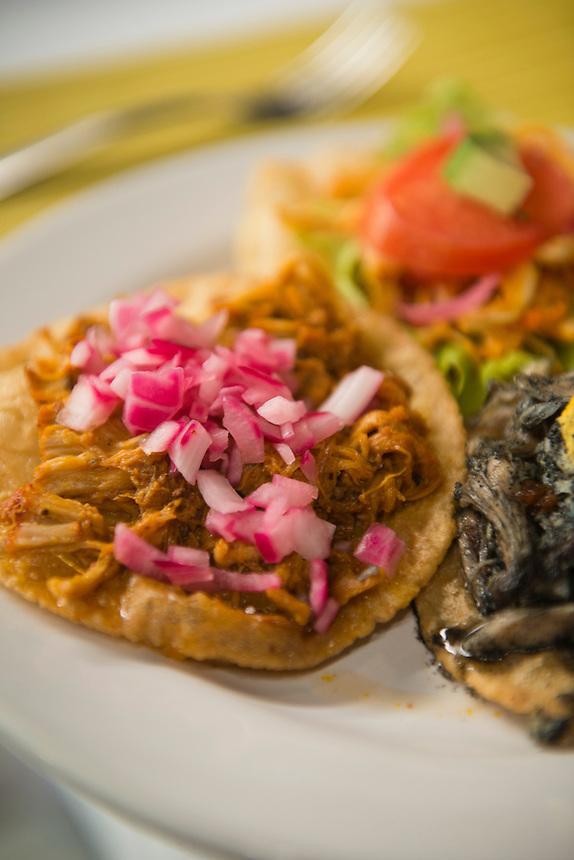 Salbutes ofRelleno Negro, turkey and Cochinita pibil. Izamal, Yucatan, Mexico