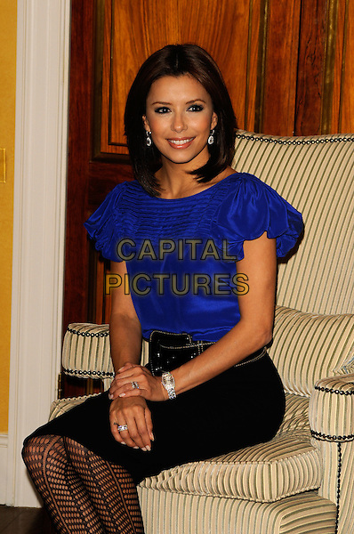 "EVA LONGORIA.Photocall for ""Over Her Dead Body"", Claridges, London, England..January 24, 2008.half 3/4 length black skirt purple blue top blouse sitting chair belt fishnet tights.CAP/CAN.©Can Nguyen/Capital Pictures"